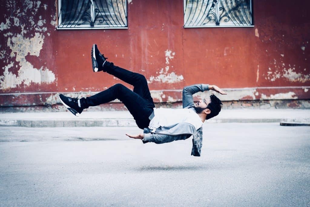 Homem aparenta estar levitando no meio de uma rua.