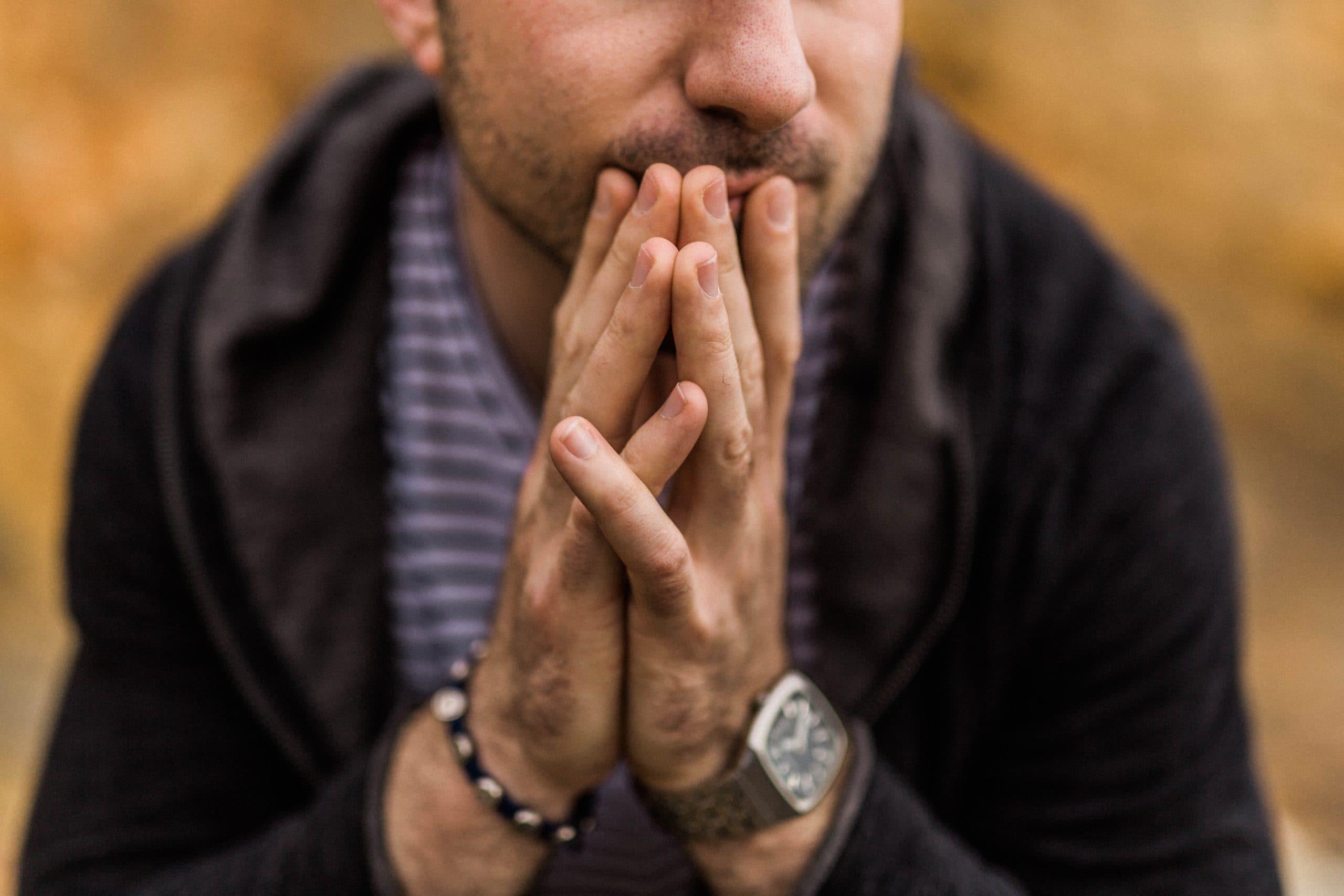 Homem sentado com as mãos juntas em frente ao rosto.