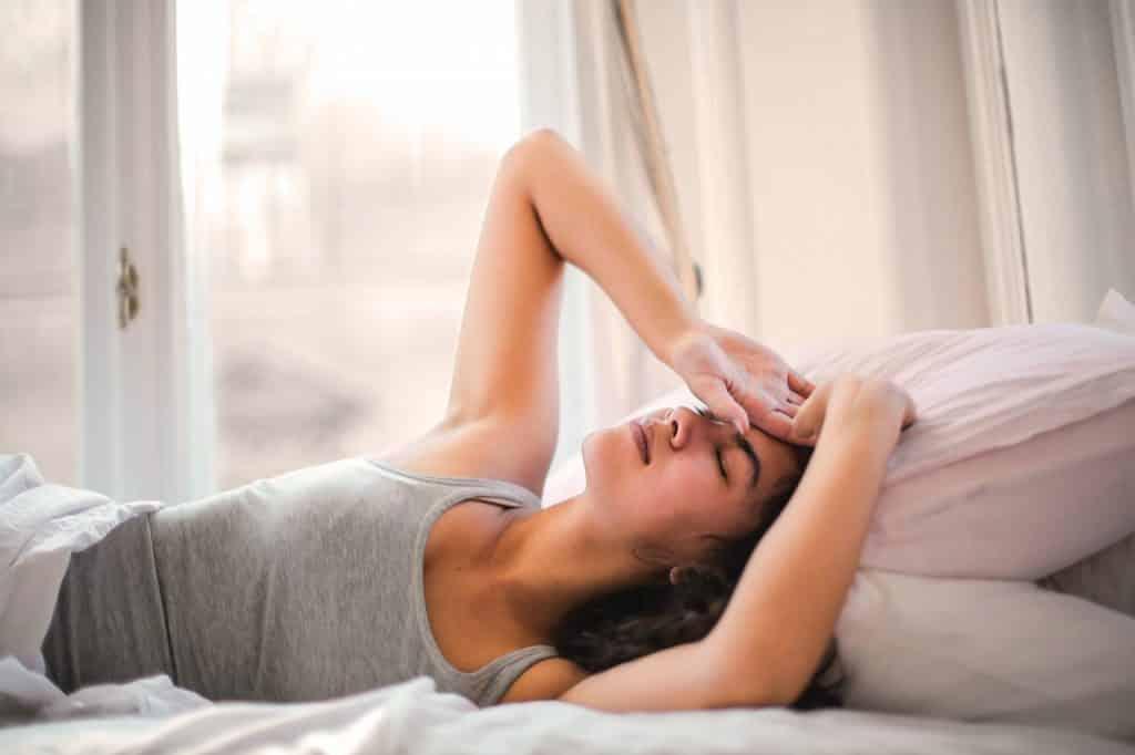 Mulher deitada na cama com as duas mãos apoiadas na cabeça.