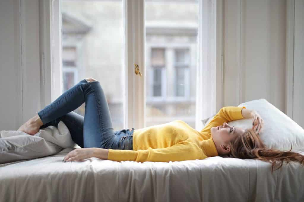 Menina de calças jeans e camiseta amarela deitada na cama olhando para cima.