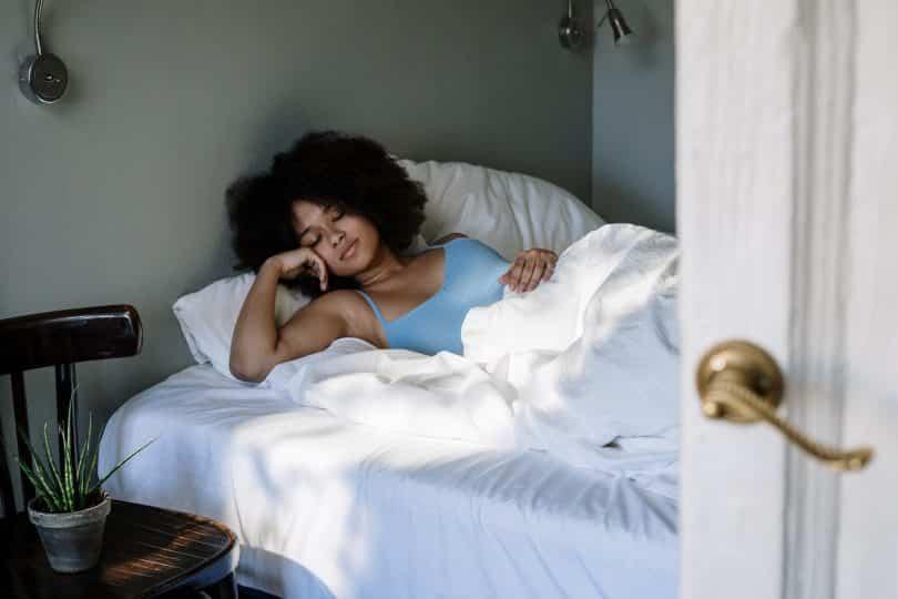 Mulher deiatda na cama dormindo ao lado de uma cadeira com planta