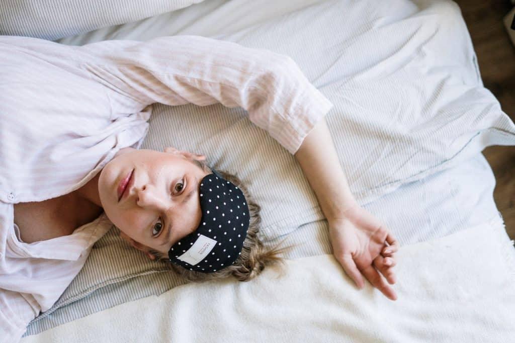 Mulher com pijama e máscara de dormir na cabeça deitada na cama olhando para cima.