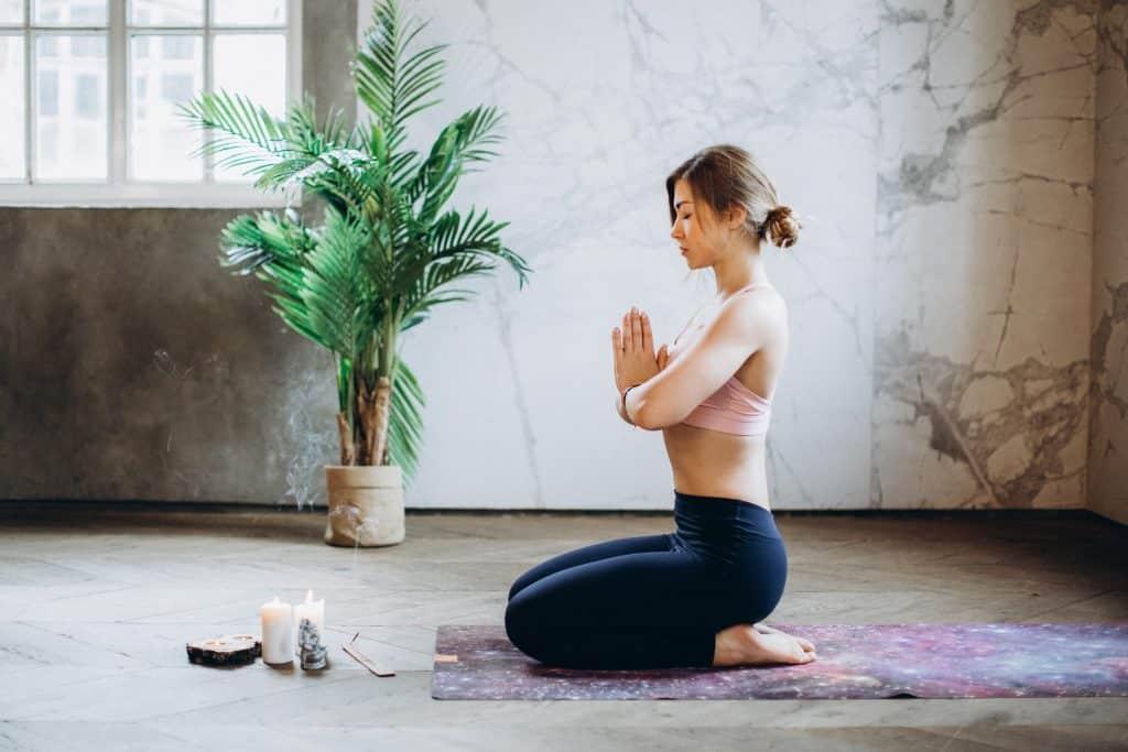 Mulher meditando em uma sala com velas e um vaso