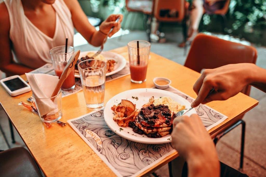 Recorte de duas pessoas sentadas na mesa comendo.