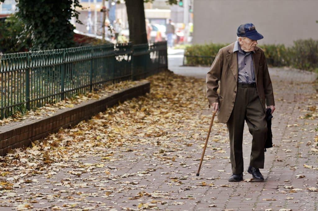 Homem idoso caminhando na rua com a ajuda de uma bengala.