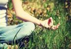Imagem recortada de um braço e perna de mulher, sentada com as pernas cruzadas em grama, com o polegar tocando o dedo indicador.