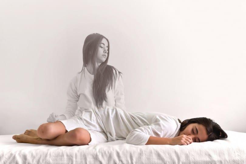 Mulher dormindo na cama enquanto sua imagem refletida se levanta sobre ela.
