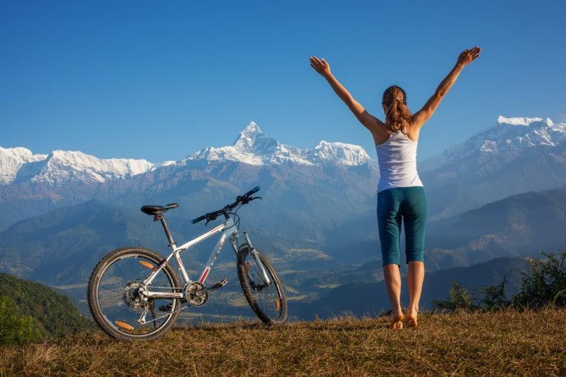 Mulher em topo de montanha, ao lado de uma bicicleta. Ela está de pé e com os braços esticados para o alto.