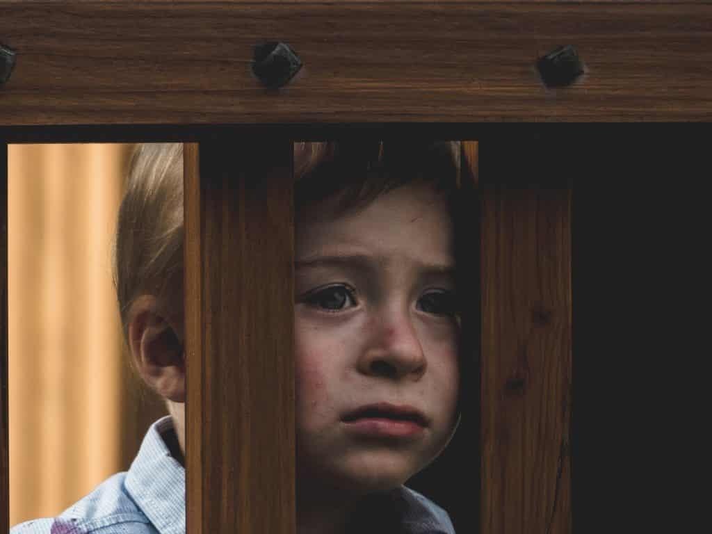 Criança olhando com tristeza para frente se segurando nas grades de madeira da escada