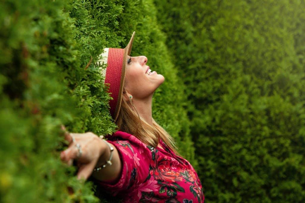 Mulher encostada em uma parede de plantas, sorrindo.
