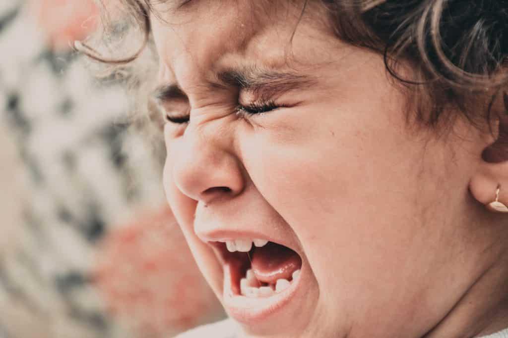 Criança de olhos fechados chorando