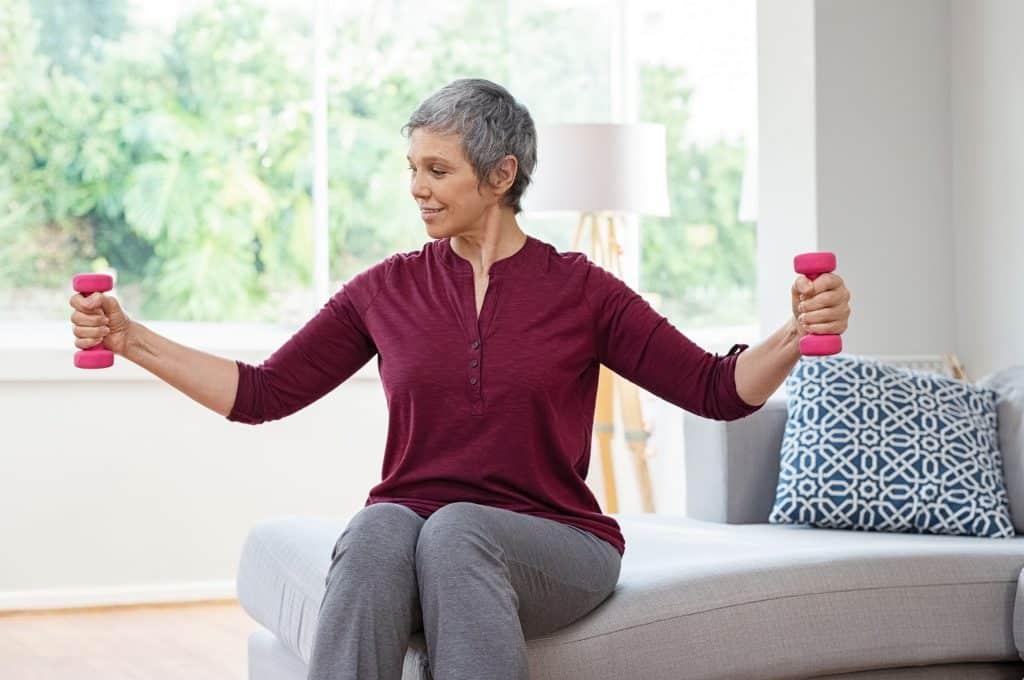 Mulher idosa sentada em uma sala com pesos de ginástica nas mãos, exercitando-se.