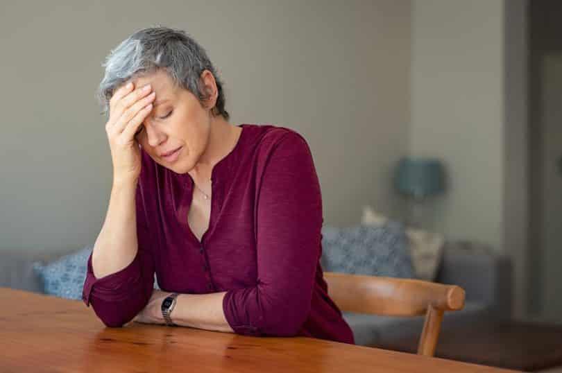 Senhora com mão na cabeça e expressão de estress