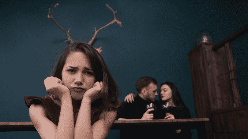 Mulher traída com representação de chifres na cabeçavendo o parceiro com outra pessoa jantando