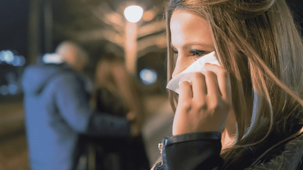 Mulher chorando ao ver que é traída por parceiro