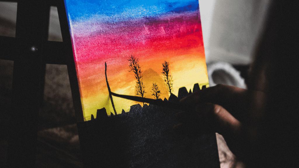 Pessoa pintando quadro de paisagem colorida