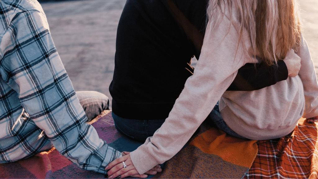 Mulher traindo o namorado segurando a mão de outro homem pelas costas do parceiro