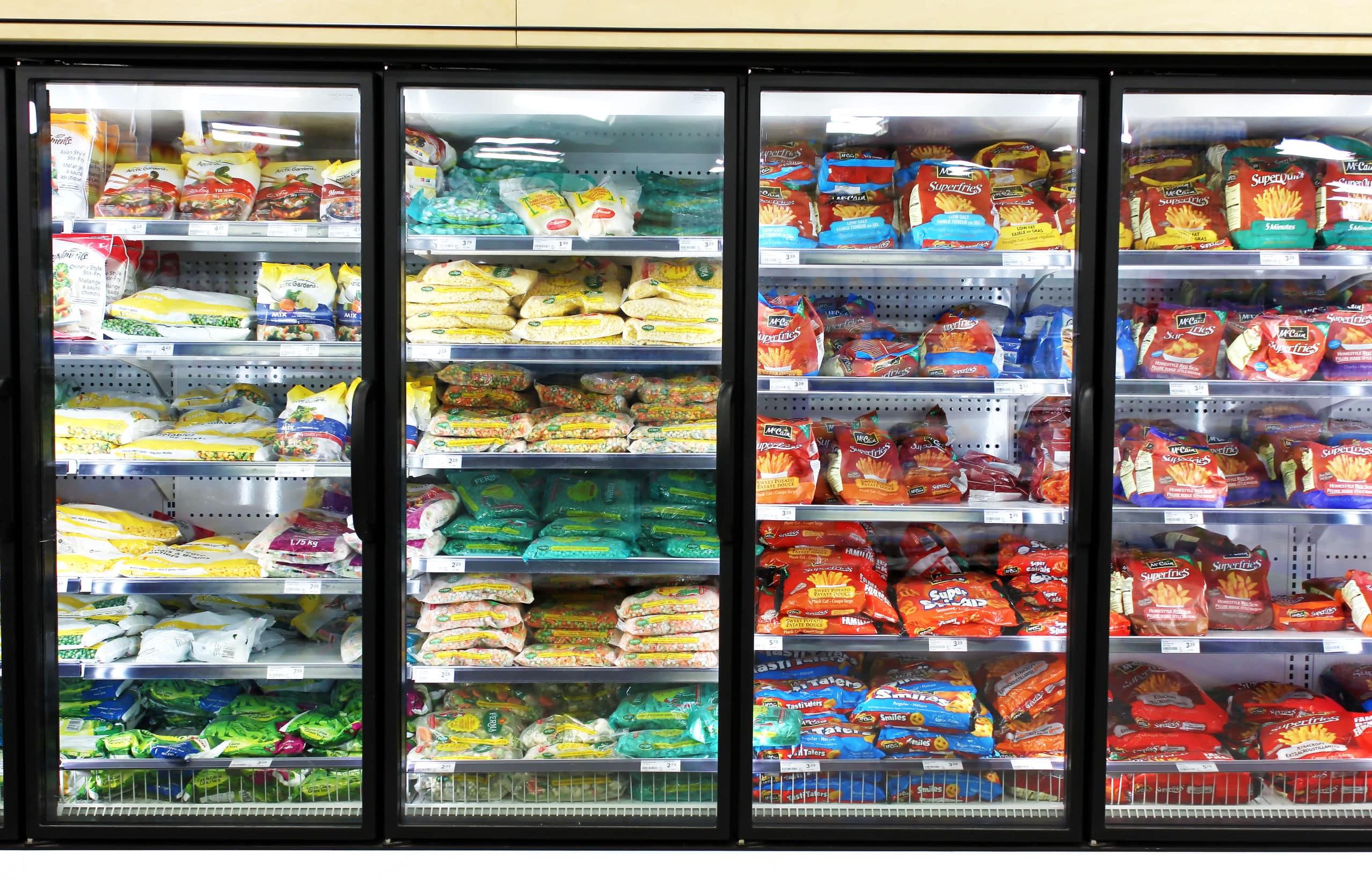 Frigorífico de mercado, com portas em vidro transparente, exibindo alimentos congelados em embalagens coloridas.