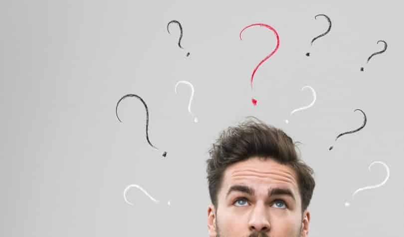Homem pensativo com sinais de interrogação ao redor de sua cabeça.