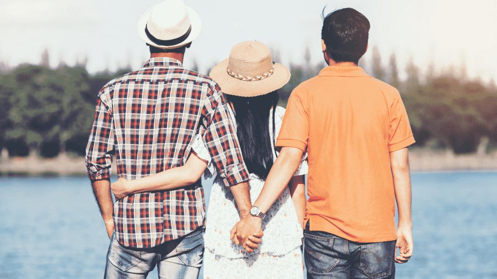 Homem traindo a namorada segurando a mão de outro homem pelas costas da parceira