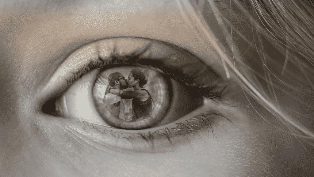 Olhos de uma mulher refletindo um casal junto