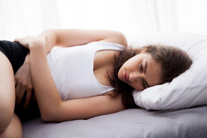 Jovem mulher deitada na cama deprimida.
