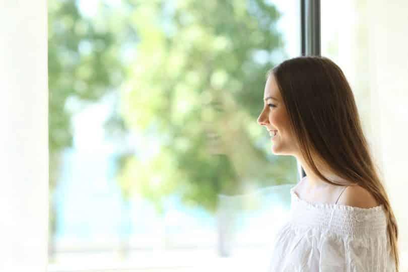 Mulher olhando pela janela sorrindo