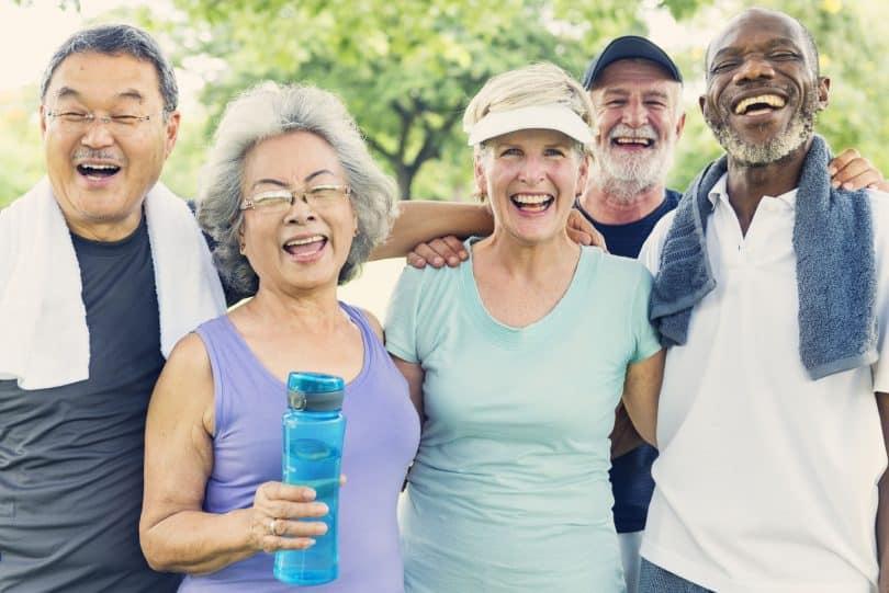 Grupo de idosos em um parque, sorrindo, com roupas de ginástica.