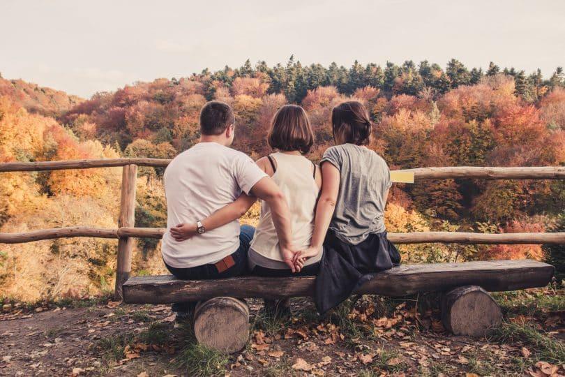 Duas mulheres e um homem sentados num banco de madeira olhando a paisagem, dois deles de mãos dadas