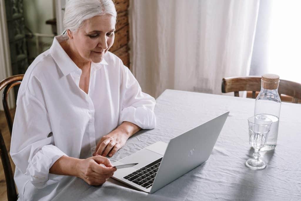 Mulher idosa sentada em uma mesa, usando o computador, que está ao lado de uma garrafa d'água.