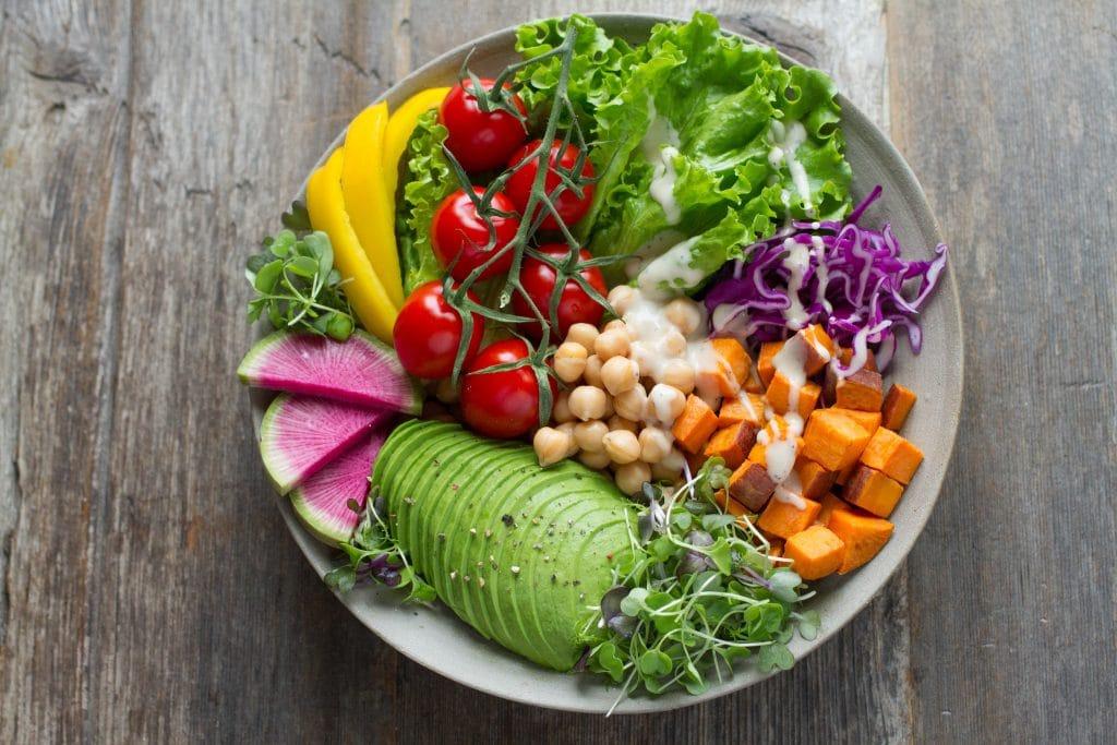 Prato com diversos vegetais. Há tomates, abacate, abóbora, repolho roxo, entre outros.