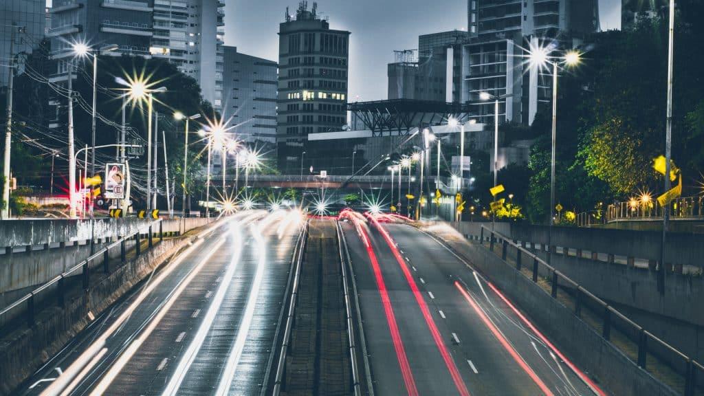 Foto em time lapse de uma rua movimentada ao começo da noite, com as luzes dos carros e dos postes de luz acesas.