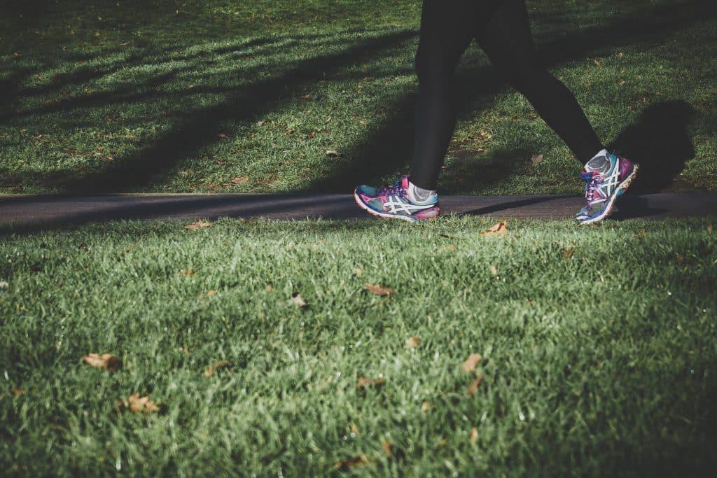 Pessoa caminhando ao lado de gramados
