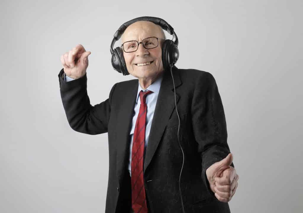 Homem idoso com roupas sociais dançando e sorrindo, com fones de ouvido.