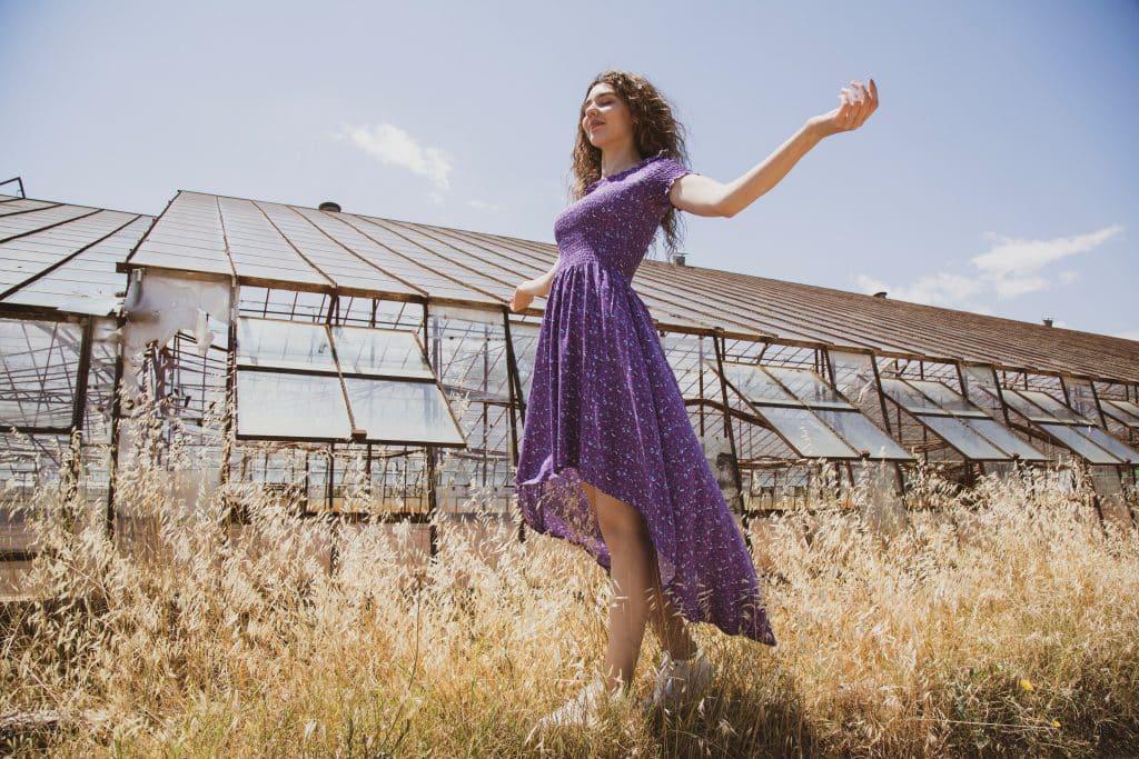 Mulher usando vestido roxo em um campo de flores