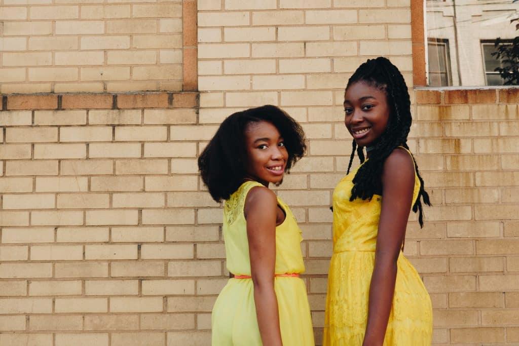 Duas mulheres usando roupas amarelas e sorrindo