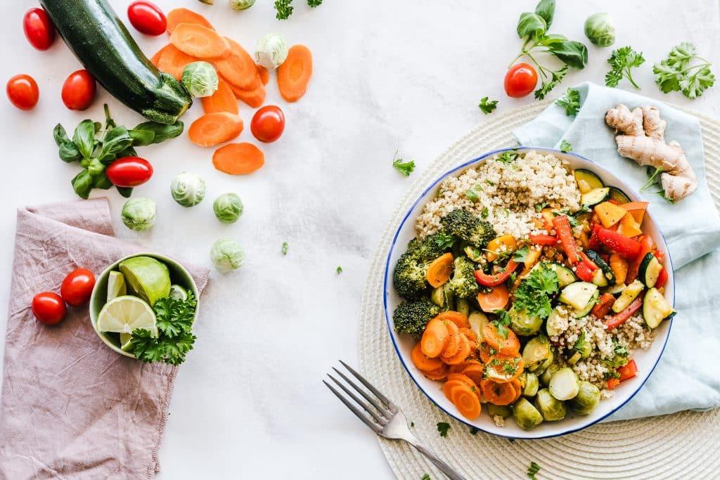 Bowl com legumes, grãos e verduras sobre uma mesa, ao lado de um garfo.