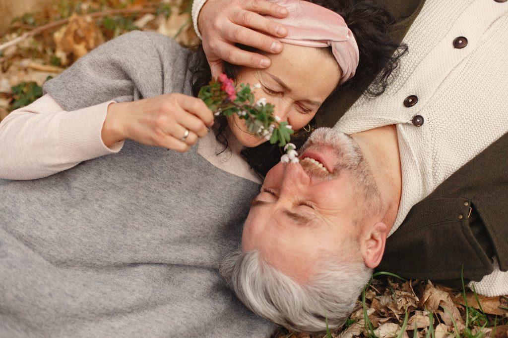 Casal de homem e mulher idosos deitado em um chão repleto de folhas, abraçados, sorrindo um para o outro.