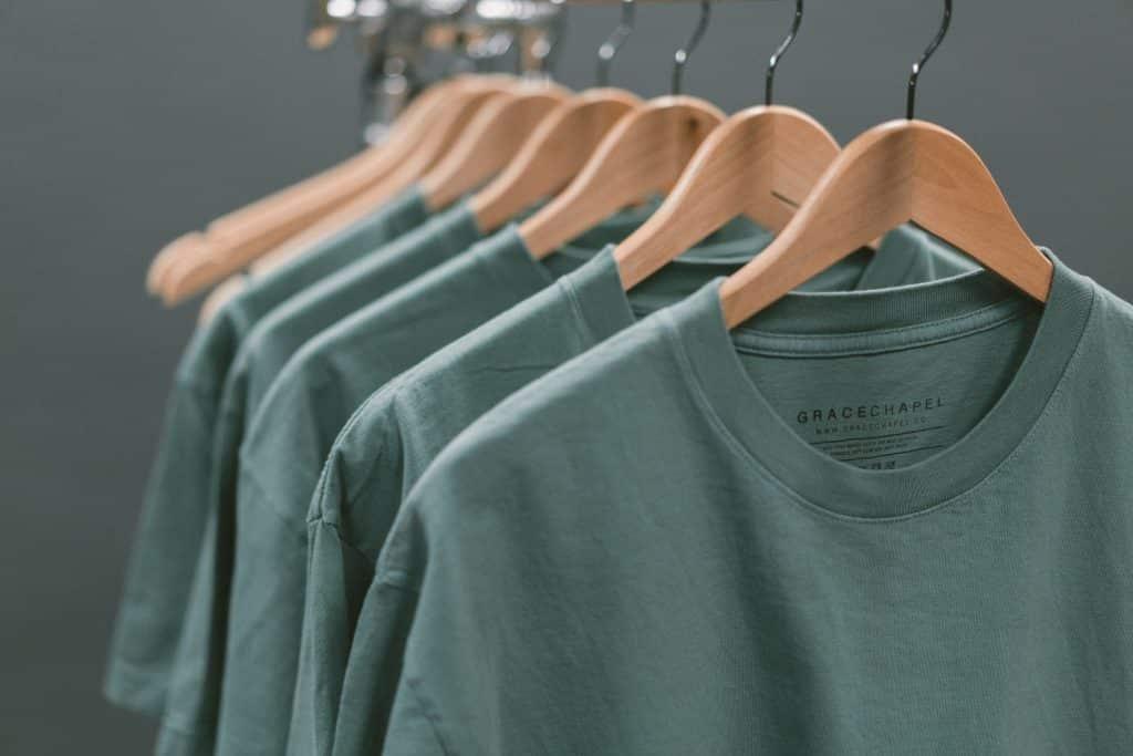 Camisetas verdes penduradas no cabine