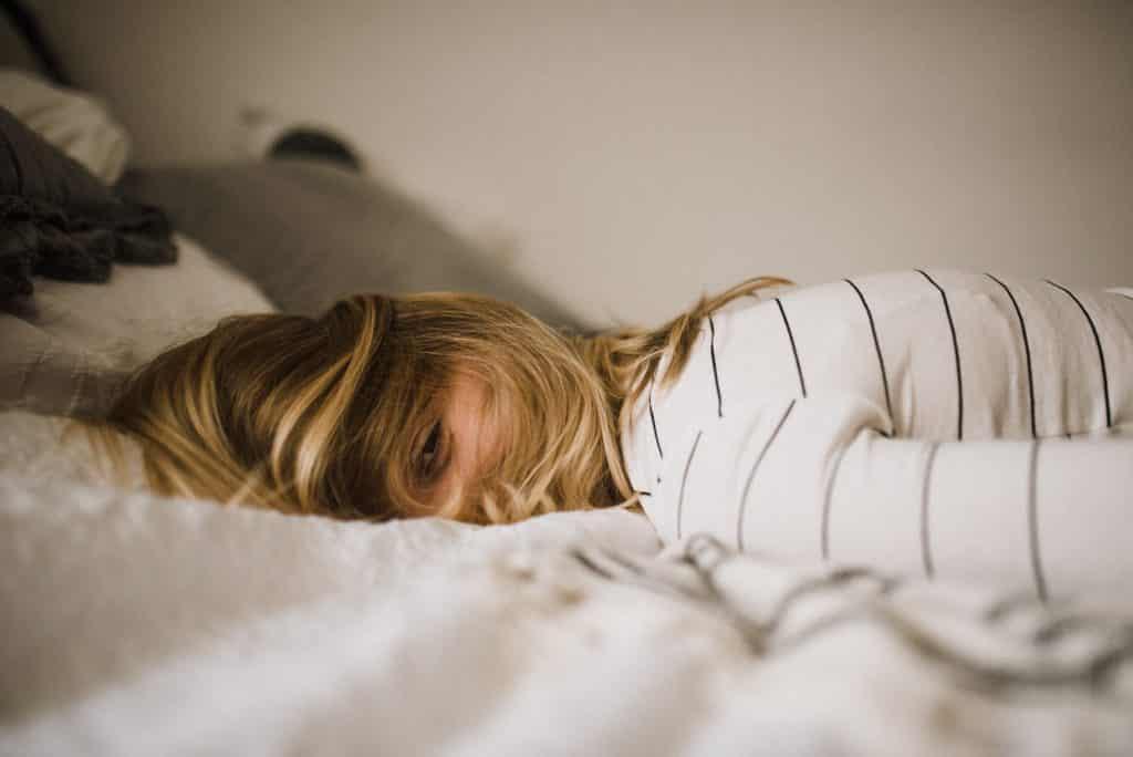 Mulher deitada na cama de barriga para baixo com seu cabelo no rosto