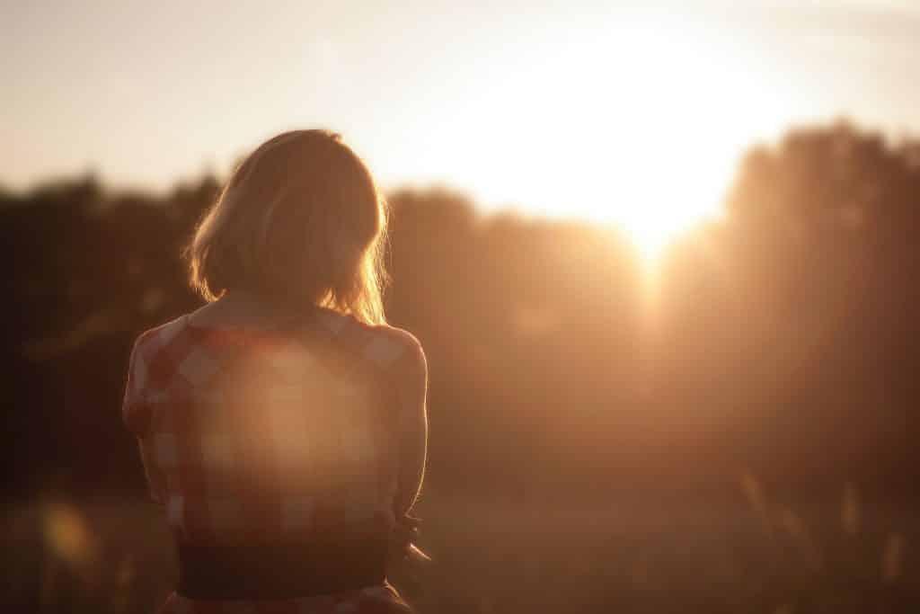 Mulher olhando para o sol entre as árvores