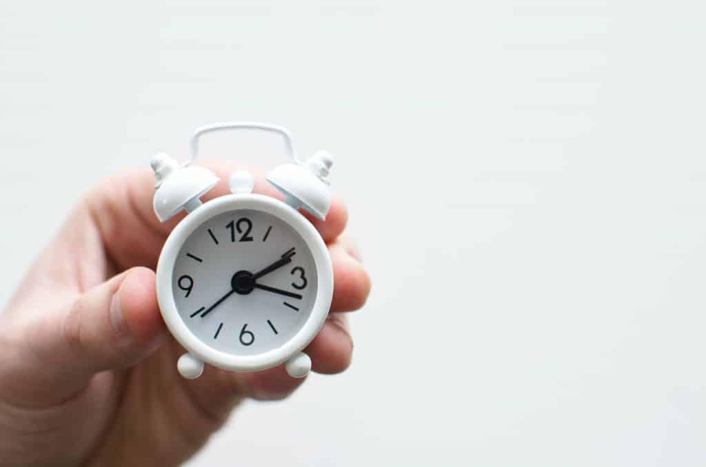 Pessoa segurando um relógio pequeno