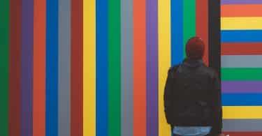 Homem olhando para parede colorida a sua frente