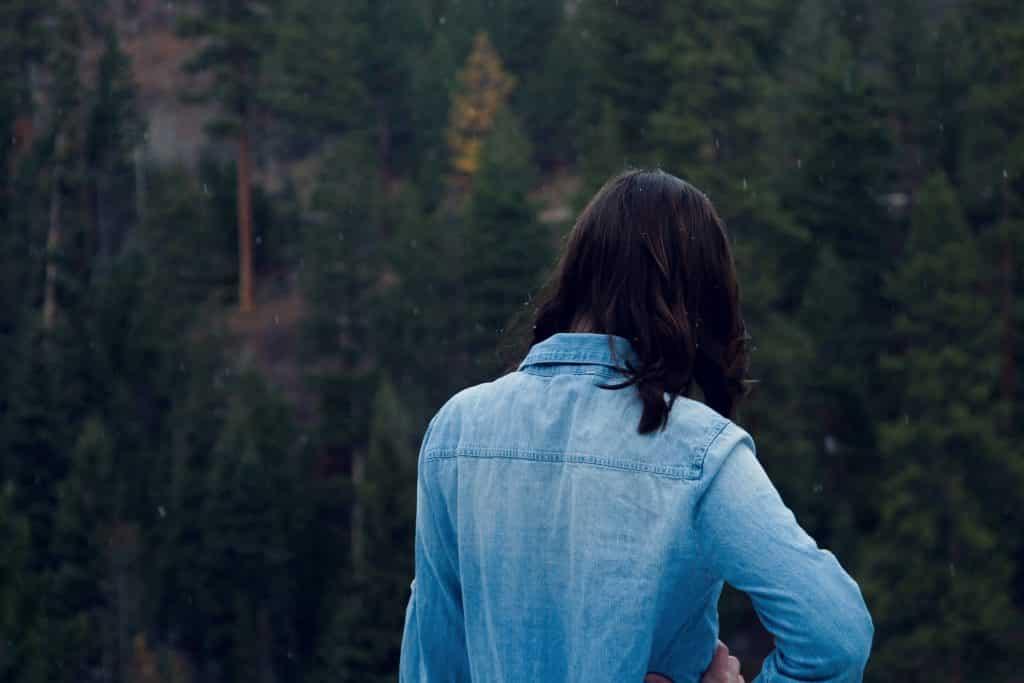 Mulher em frente a algumas arvores usando uma blusa jeans