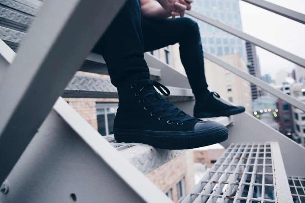 Homem sentado em uma escada usando tênis preto