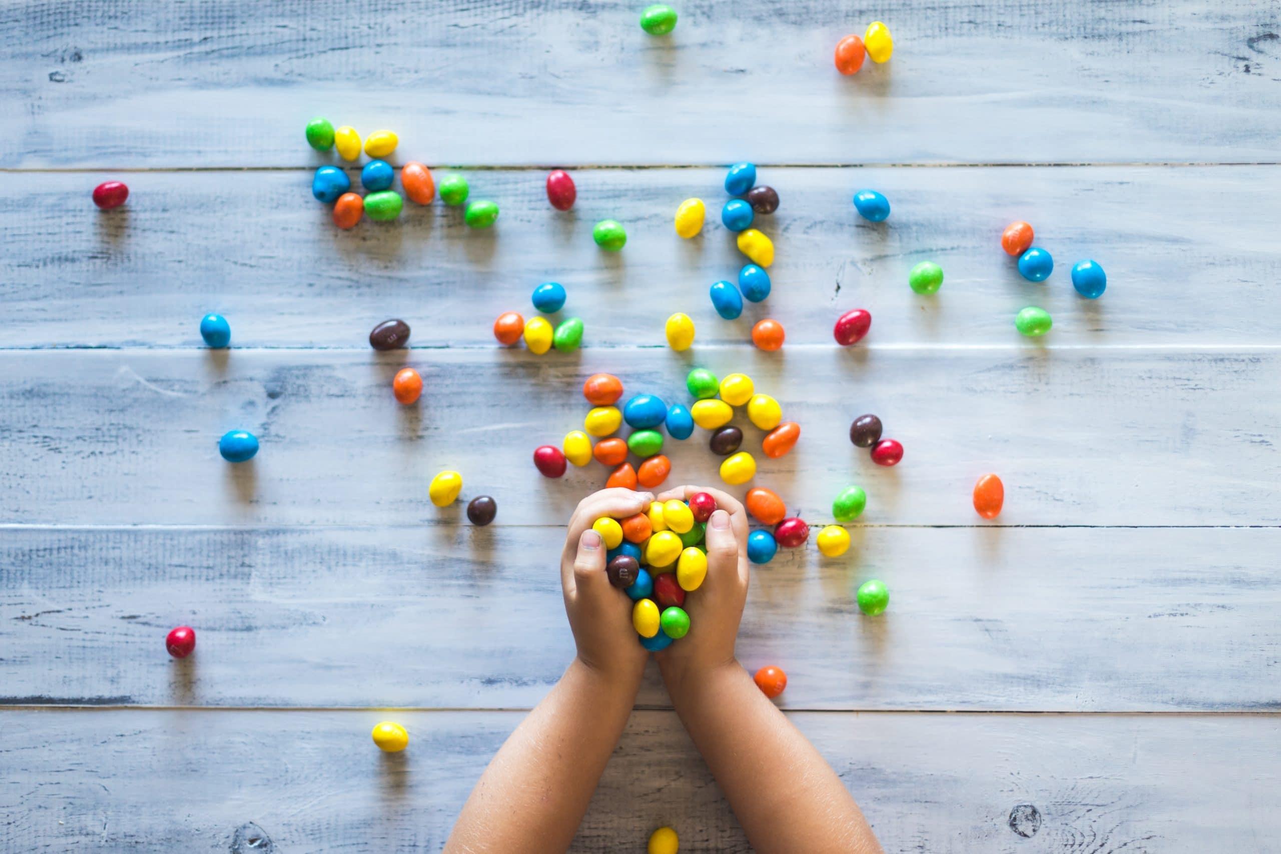 Mãos segurando um punhado de dos coloridos. Há alguns desses doces espalhados pela mesa de madeira que há abaixo das mãos.