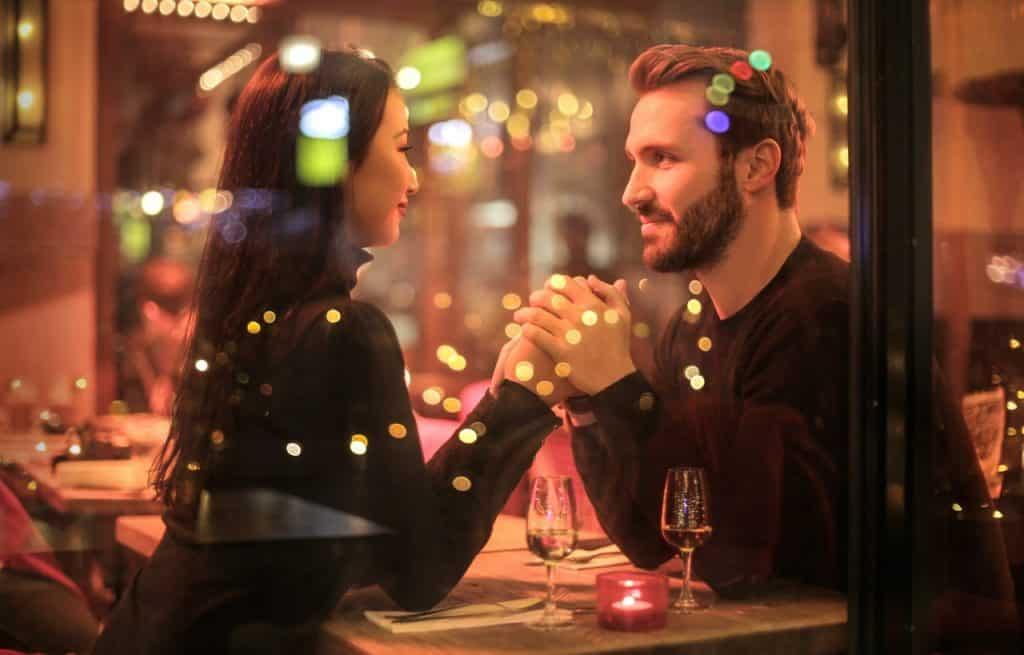 Casal de mãos dadas sentados em um restaurante