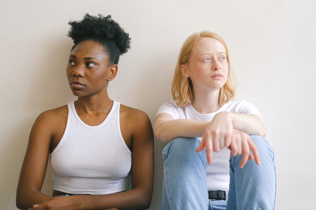 Duas mulheres sentadas no chão.