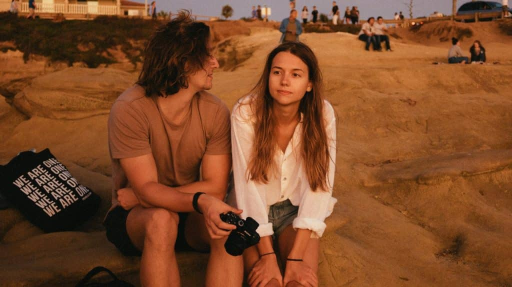 Homem e mulher sentados na areia, conversando.