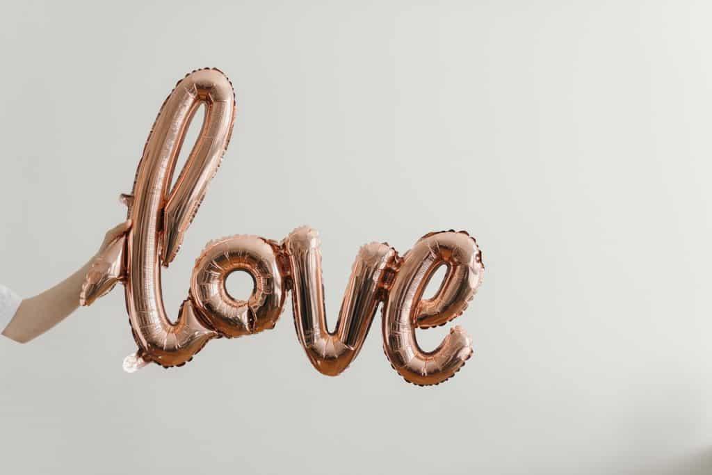 """Pessoa segurando um balão em forma da palavra """"love""""."""